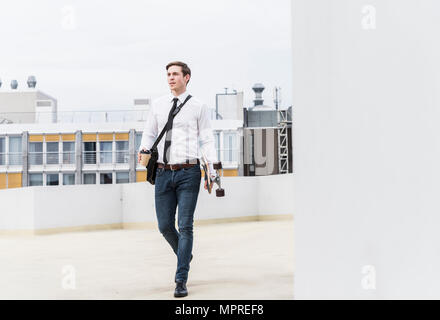 Businessman with takeaway coffee and skateboard walking at parking garage - Stock Photo