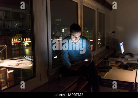 Businessman sitting on window sill in office at night using tablet - Stock Photo