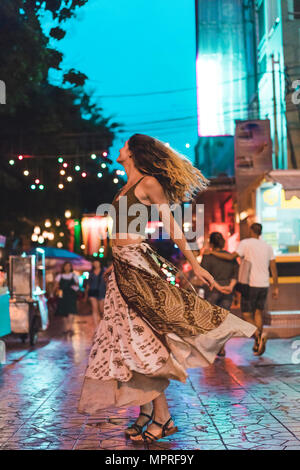 Thailand, Bangkok, young woman in the city dancing on the street at night - Stock Photo