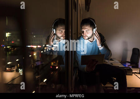 Businessman sitting on window sill in office at night listening music with headphones - Stock Photo
