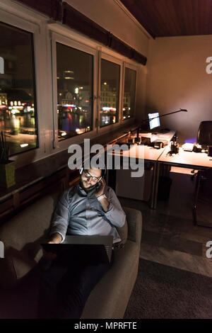 Businessman in office sitting on the couch at night using laptop and headphones - Stock Photo