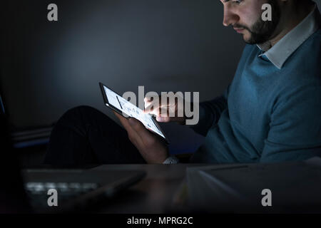Businessman working on tablet in office at night - Stock Photo