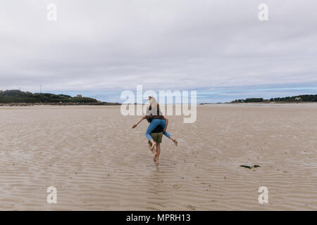 France, Brittany, Guisseny, young man running  carrying girlfriend piggyback on the beach - Stock Photo