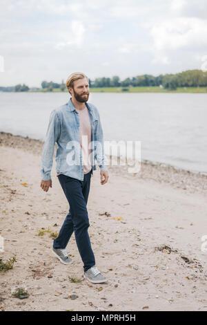 Germany, Duesseldorf, man walking on the beach - Stock Photo