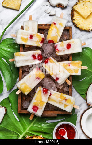 Pina Colada popsicles with candied cherries and pineapple on leaf - Stock Photo