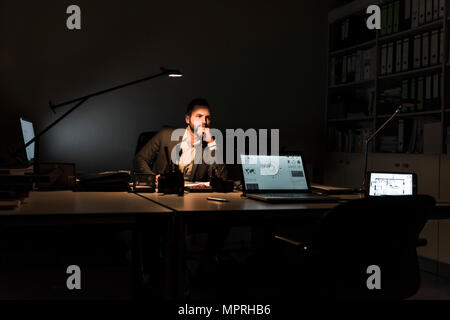 Pensive businessman sitting at desk in office at night - Stock Photo