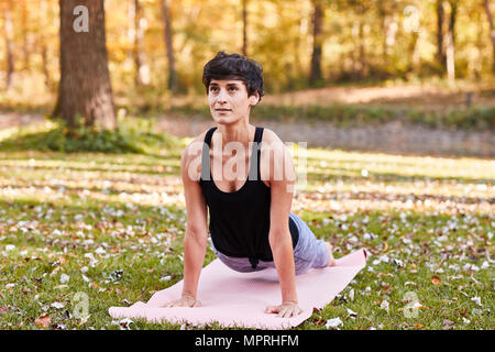 Mid adult woman in forest practicing yoga, cobra pose - Stock Photo