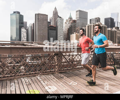 USA, New York City, two men running on Brooklyn Brige with data on the ground - Stock Photo