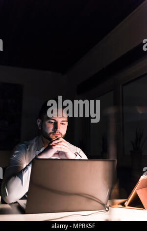 Portrait of businessman sitting at desk  in office at night looking at laptop - Stock Photo
