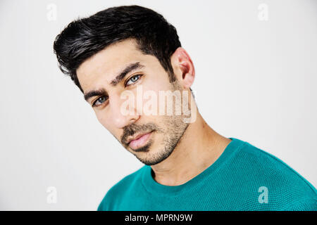 Portrait of serious young man with stubble - Stock Photo