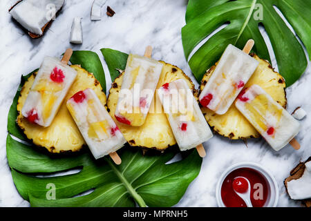 Pina Colada popsicles with candied cherries and pineapple - Stock Photo