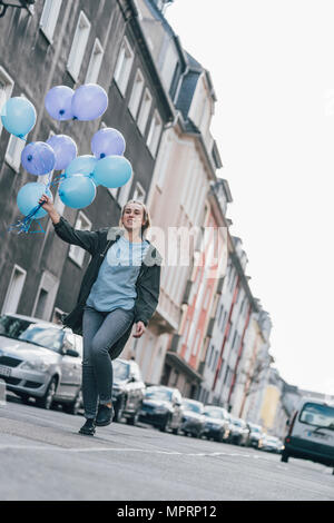 Happy woman with blue balloons walking on the street - Stock Photo