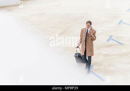 Businessman with rolling suitcase and smartphone walking at parking garage - Stock Photo