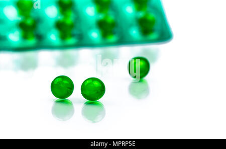 Green round soft capsule pills on blurred background of blister pack with space. Ayurvedic medicine for indigestion, gas and acidity. Herbal medicine  - Stock Photo
