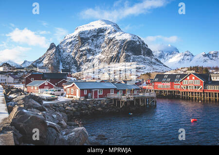 Beautiful super wide-angle winter snowy view of fishing village A, Norway, Lofoten Islands, with skyline, mountains, famous fishing village with red f - Stock Photo