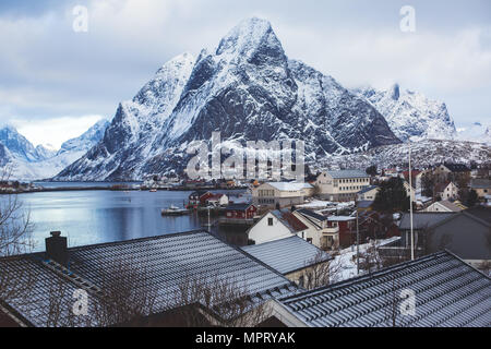 Beautiful super wide-angle winter snowy view of Reine, Norway, Lofoten Islands, with skyline, mountains, famous fishing village with red fishing cabin - Stock Photo