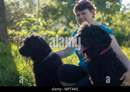 A woman and her two black Russian Terriers are on a walk in the Park - Stock Photo