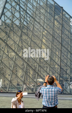 tourists doing selfie in front of Pyramid of Louvre Museum, Paris, France - Stock Photo