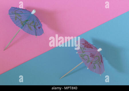 Creative view of a cocktail umbrella on a two-tone background - pink and blue. Conceptual image of summer. Minimalism.  Summertime. Top view. - Stock Photo