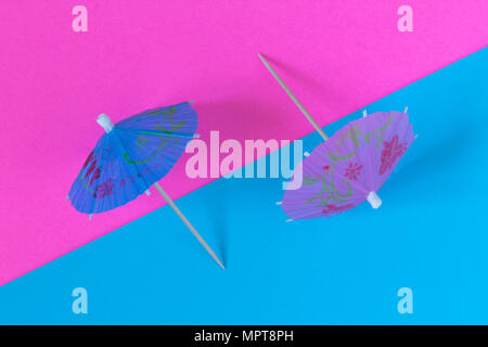 Creative view of a cocktail umbrella on a two-tone background - pink and blue. Conceptual image of summer. Minimalism. Abstraction. Summertime. Top vi - Stock Photo