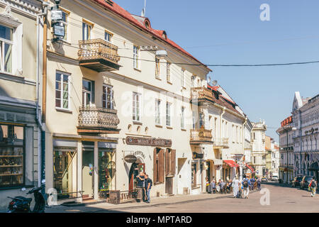 People walking in Vilnius old town street in sunny day. - Stock Photo