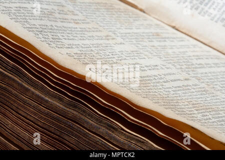 A close up / macro of an old 19th century Bible, open in the Psalms, with some of the spine visible - Stock Photo
