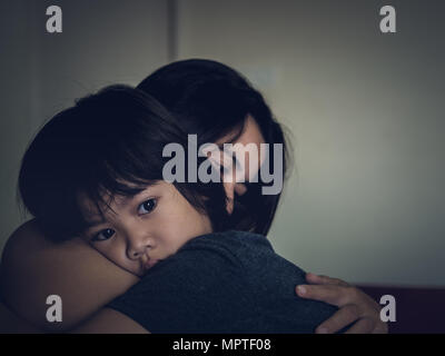 Mother and child, cute little boy resting on her mother's shoulder. Young mother holding her sad boy at home. - Stock Photo