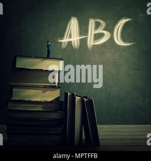 Teacher stand on the top of a huge books pile looking at the blackboard with ABC letters written. Education and knowledge concept. Teaching practice f - Stock Photo