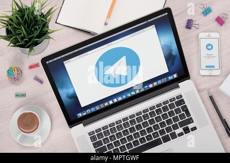 Telegram messenger logo on laptop and smartphone screens. - Stock Photo