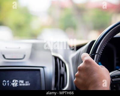 Closeup driver hands holding steering wheel while driving on the road. - Stock Photo