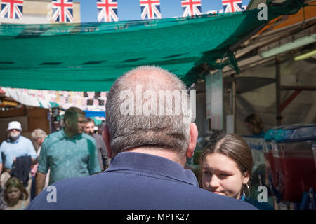 Close-up, shallow focus of an adult male seen walking away from the camera. He is located in an open air market during British celebrations. - Stock Photo
