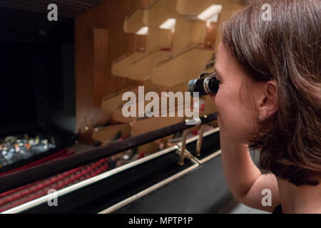 A woman is watching the orchestra in a theatre with opera glasses - Stock Photo