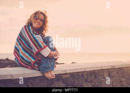 nice cute lady with swirl hair smiling at you while sit down near the ocean coast. poncho and hippy clothes to represent freedom concept. vacation sty - Stock Photo