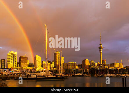 new zealand auckland new zealand north island rainbow after rain storm over auckland harbour waterfront weird colour sky stormy sky auckland nz - Stock Photo