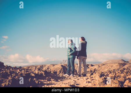 Senior mother and 45 year old son spend time together walking on an isolated path - Stock Photo