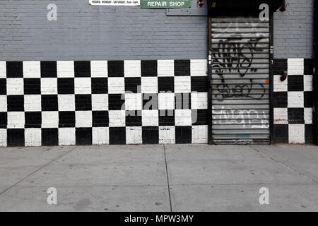 Checkered flag painted on car repair storefront in New York City - Stock Photo