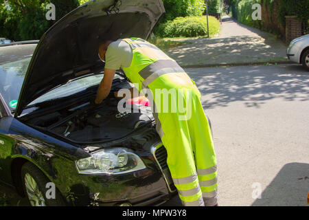 HANNOVER / GERMANY - MAY 21, 2018: Service man from ADAC, german automobile club repairs a broken car. - Stock Photo