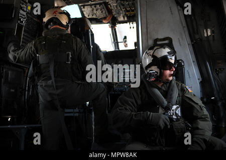 "170413-N-UX013-654  NORFOLK (April 13, 2017) Naval Air Crewman (Helicopter) 2nd Class Stephen Prickett, right, watches the flight line as they lift off in an MH-53E Sea Dragon helicopter assigned to ""Vanguard"" of Helicopter Mine Countermeasures Squadron (HM) 14 during a formation and training flight. HM-14 maintains a worldwide 72-hour airborne mine countermeasures rapid deployment posture, a two aircraft forward-deployed AMCM and vertical onboard delivery capability in the 7th Fleet area of responsibility. (U.S. Navy photo by Mass Communication Specialist 3rd Class Jonathan Clay/Released) - Stock Photo"