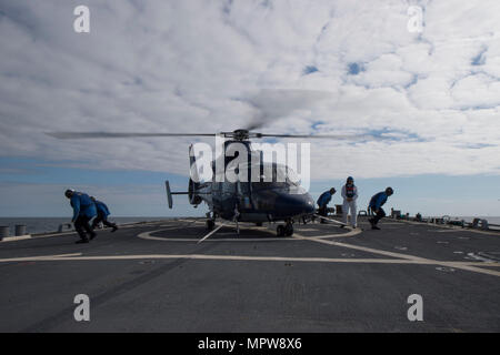 170417-N-ZE250-317   ATLANTIC OCEAN (April 17, 2017) - A chock and chain team from USS Carney (DDG 64) moves away from a Royal Navy HH-65 Dauphin helicopter while being observed by a Royal Navy Flag Officer Sea Training (FOST) facilitator in the Atlantic Ocean April 17, 2017. Carney, an Arleigh Burke-class guided-missile destroyer, forward-deployed to Rota, Spain, is conducting its third patrol in the U.S. 6th Fleet area of operations in support of U.S. national security interests in Europe. (U.S. Navy photo by Mass Communication Specialist 3rd Class Weston Jones/Released) - Stock Photo