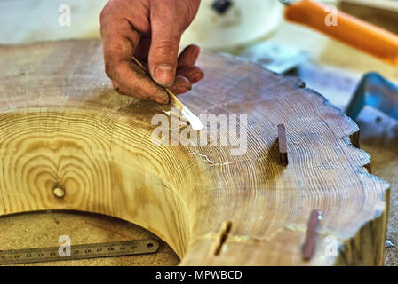 Close-up of the insertion of dowels in a joinery workshop - Stock Photo