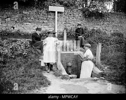 Collecting water from the village pump, Barton Hartshorn, Buckinghamshire, 1901. Artist: Alfred Newton & Sons. - Stock Photo