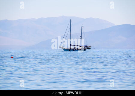 Sailboat in clear sunny weather on the calm seas. Mediterranean sea. Summer vacation. The concept of relaxation. Destination European tourism. Morning seascape with mountains background. - Stock Photo