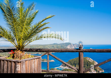 View on the bay and beach Paleokastritsa with flowers, palm tree and blue sea water on the Island Corfu, Greece.View point in Lakones. Copy space - Stock Photo