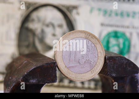 Financial dominance: one euro in a vice against the background of the American dollar with space for text - Stock Photo
