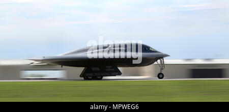 A B-2 Spirit stealth bomber assigned to the 509th and 131st Bomb Wings (BW) races down the flightline during takeoff at Whiteman Air Force Base, Mo., April 20, 2017. The B-2 Spirit is a multi-role bomber capable of delivering both conventional and nuclear munitions. Its low-observable, or 'stealth,' characteristics give it the unique ability to penetrate an enemy's most sophisticated defenses and threaten its most valued, and heavily defended, targets. (U.S. Air Force photo by Senior Airman Joel Pfiester) - Stock Photo