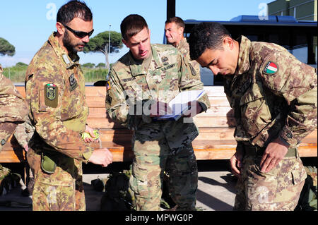 Sgt. Christopher Beseda, a U.S. Army Paratrooper from Alpha Company, 1st Battalion, 503rd Infantry Regiment, 173rd Airborne Brigade inspects an Italian Army Folgore Brigade Paratrooper before the jump at San Giusto military airport during a JumpmasterCourse, Pisa, Italy, April 21, 2017. (photo by Elena Baladelli /released). - Stock Photo
