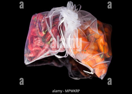 Two white gas transparent sacks with small orange and red habanero peppers on black background with reflection - Stock Photo