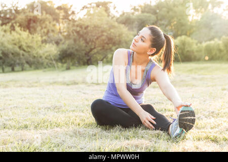 Sporty woman warming up before workout, yoga or fitness outdoor in sunrise or sunset. Sun flares. - Stock Photo