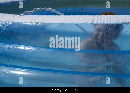 Inflatable paddling pool: a unidentifiable boy playing with a garden hose in an inflatable paddling pool - Stock Photo