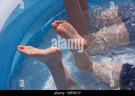 Inflatable paddling pool: two unidentifiable boys playing in an inflatable paddling pool - Stock Photo